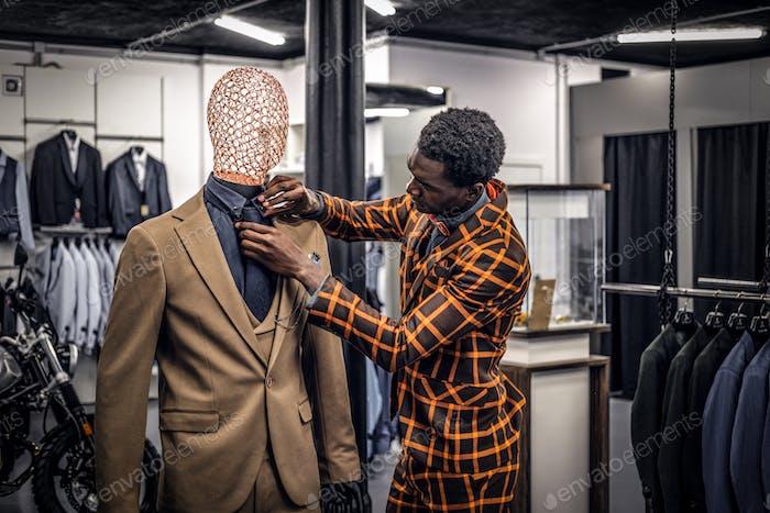 Красивый элегантно одетый афро-американский мужчина в классическом магазине мужской одежды