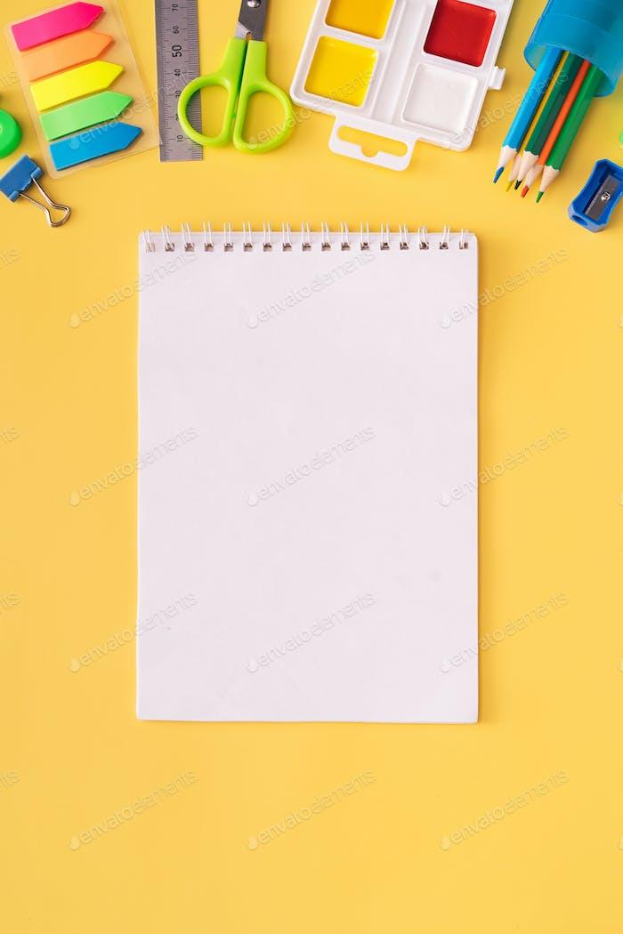 Cuaderno en blanco con material escolar sobre fondo amarillo