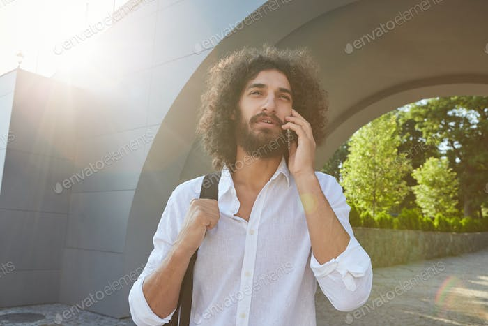 Attractive young curly male with beard walking through city park, squinting from the sun