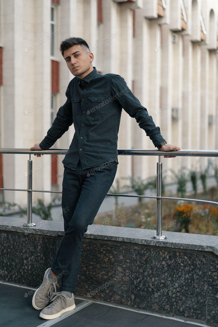 Porträt eines hübschen jungen, lässigen Mannes, der auf dem Straßenhintergro posiert