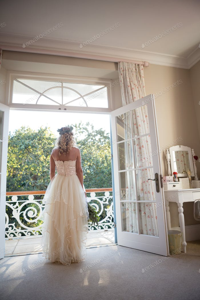 Rear view of bride standing at doorway at home