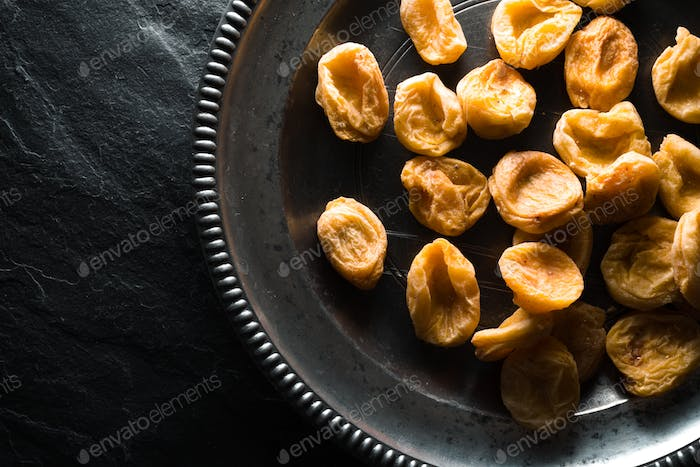 Dry dried apricots on a tin plate on a stone background closeup