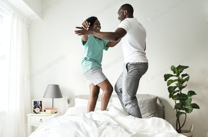Black couple jumping on bed together