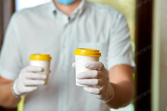 Delivery man in protective mask and gloves, employee hold takeaway cup of coffee, coronavirus