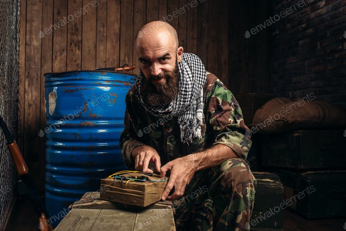 Bearded terrorist in uniform cooking a bomb