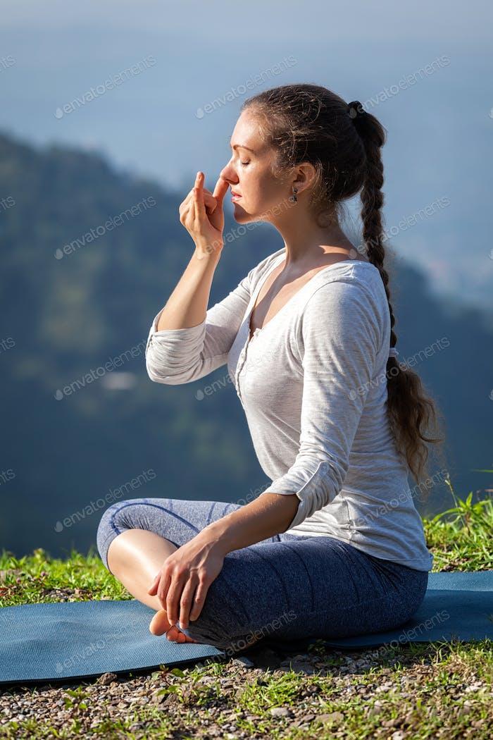 Frau praktiziert pranayama in Lotus Pose im freien