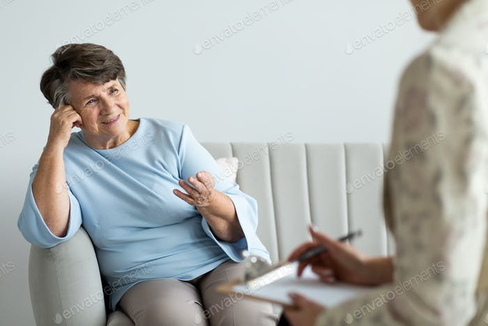 Smiling satisfied senior woman talking to a psychotherapist