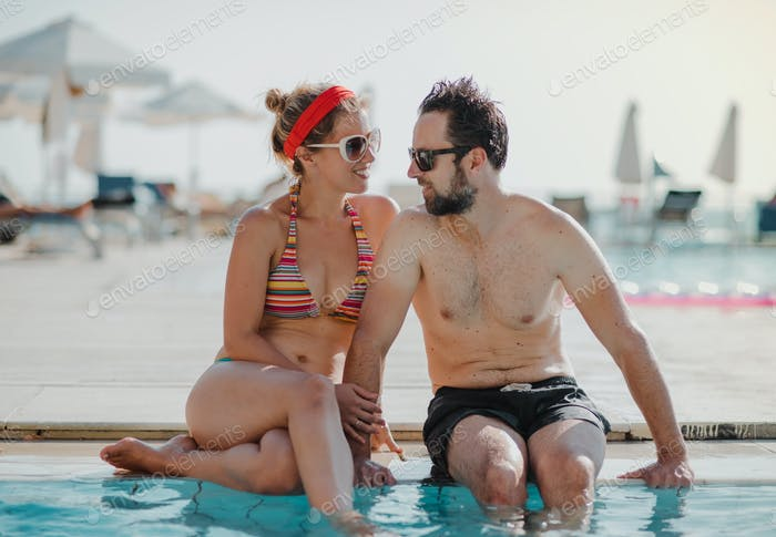 A couple in swimsuit sitting by the swimming pool on summer holiday.