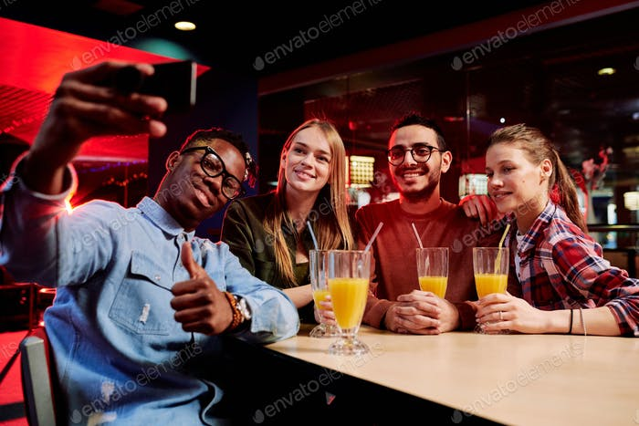 Young African man showing thumb up while making selfie with his friends