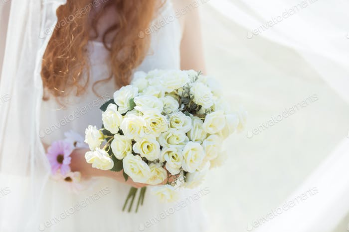 Bride holding a bunch of white roses