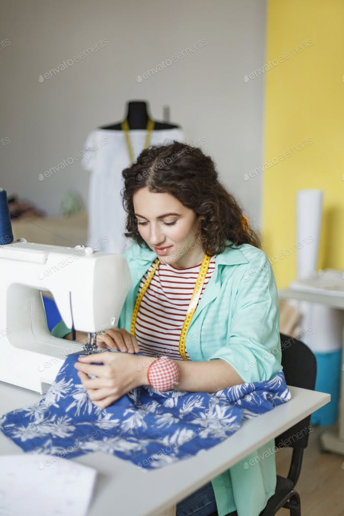 Pretty seamstress in colorful shirt and striped T-shirt dreamily