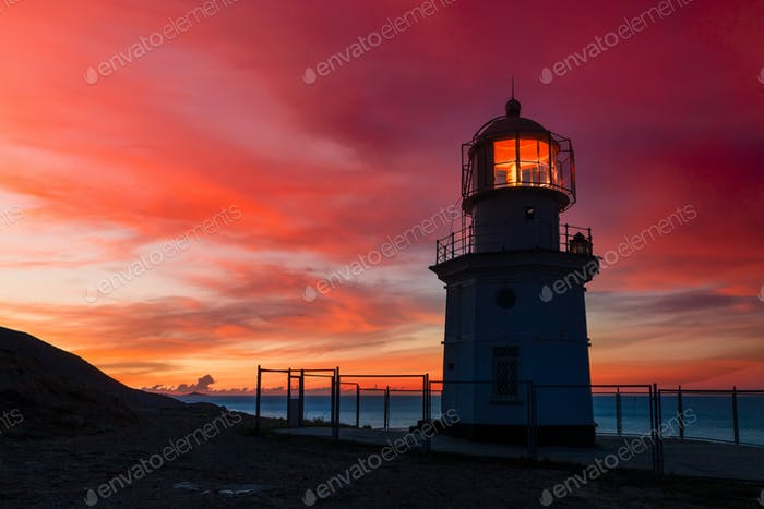 Lighthouse at sunset on the ocean. Beautiful landscape