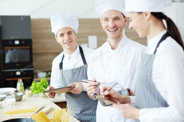 Positiver Koch beim Kochen mit jungen Mitarbeitern