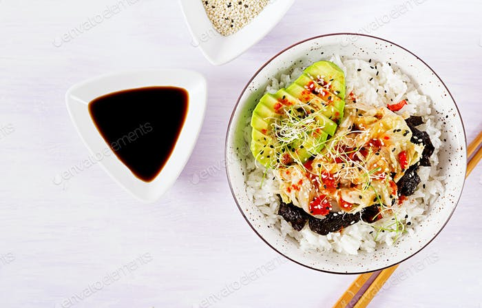 Vegan salad  with rice, pickled kimchi cabbage, avocado,  nori and sesame on bowl.