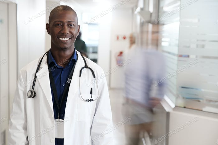 Portrait Of Smiling Male Doctor Wearing White Coat With Stethoscope In Busy Hospital Corridor