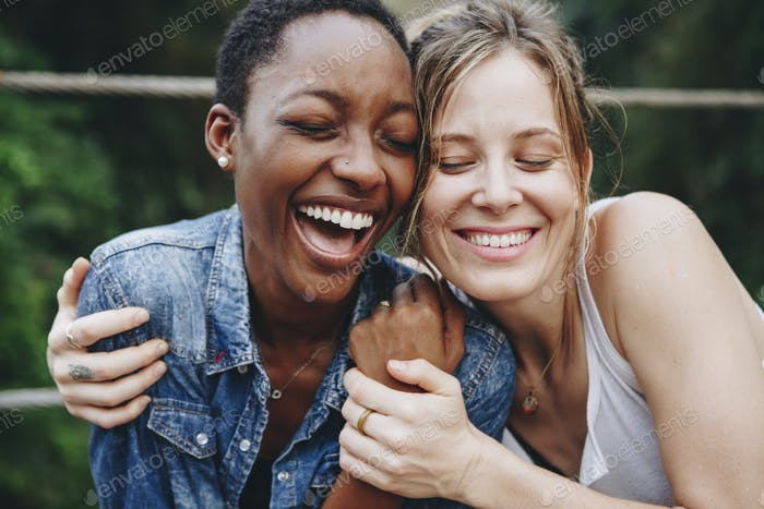Happy black woman laughing with her friend