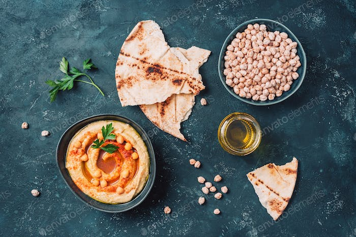 Chickpeas hummus, olive oil, raw chickpeas, smoked paprika, pita on dark background. Middle eastern