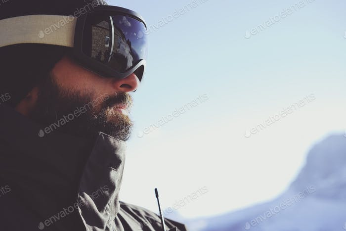 Close-up portrait of bearded young snowboarded in sunglass mask, at the ski resort