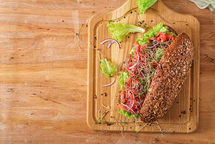 Salmon sandwich - smorrebrod with cheese cream and microgreen on wooden table. Top view