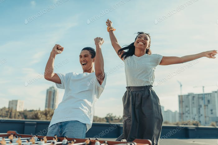 happy couple celebrating victory in table football on roof