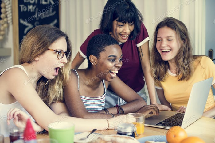 Group of diverse friends looking at computer laptop with surprise face expression