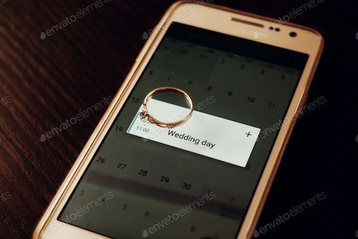 goldener Verlobungsring am Telefon mit Kalender mit Hochzeitstag. Zeit für Hochzeit