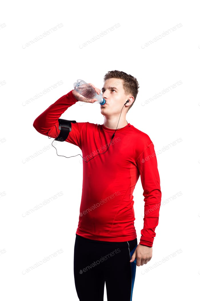 Teenage boy with smartphone and earphones, drinking water. Isolated.