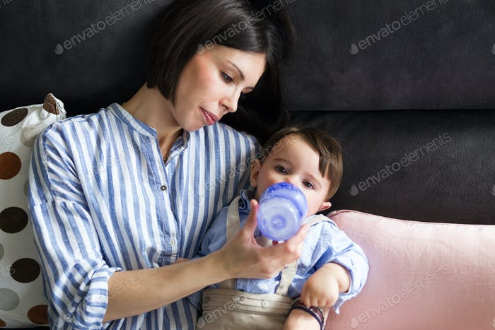 Pretty young mother feeding her baby with milk on feeding bottle in the living room of home.