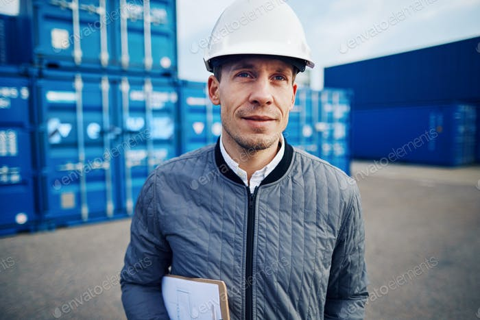 Smiling freight manager standing in a large container yard