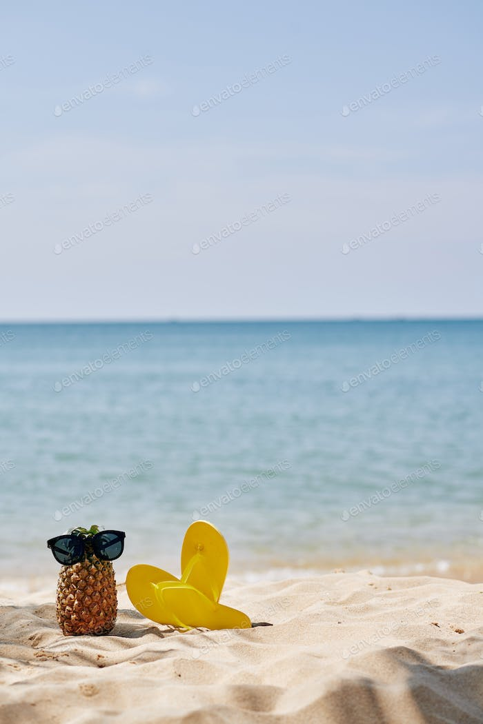 Flip-flops and pineapple on beach