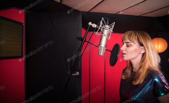 Junge Sängerin während der Musiksession im Tonstudio