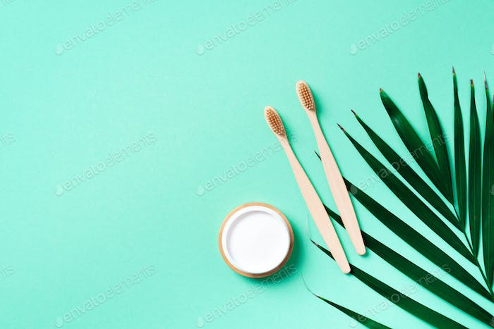 Zero waste concept. Natural toothpaste from baking soda and bamboo toothbrush on trendy green
