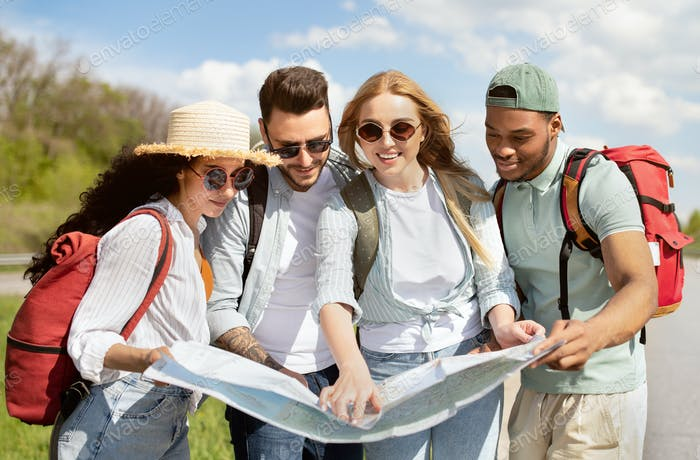 Local travel. Group of young people studying map on roadside, checking their destination point