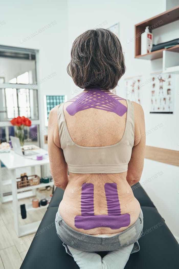 Female patient receiving the kinesiology taping treatment
