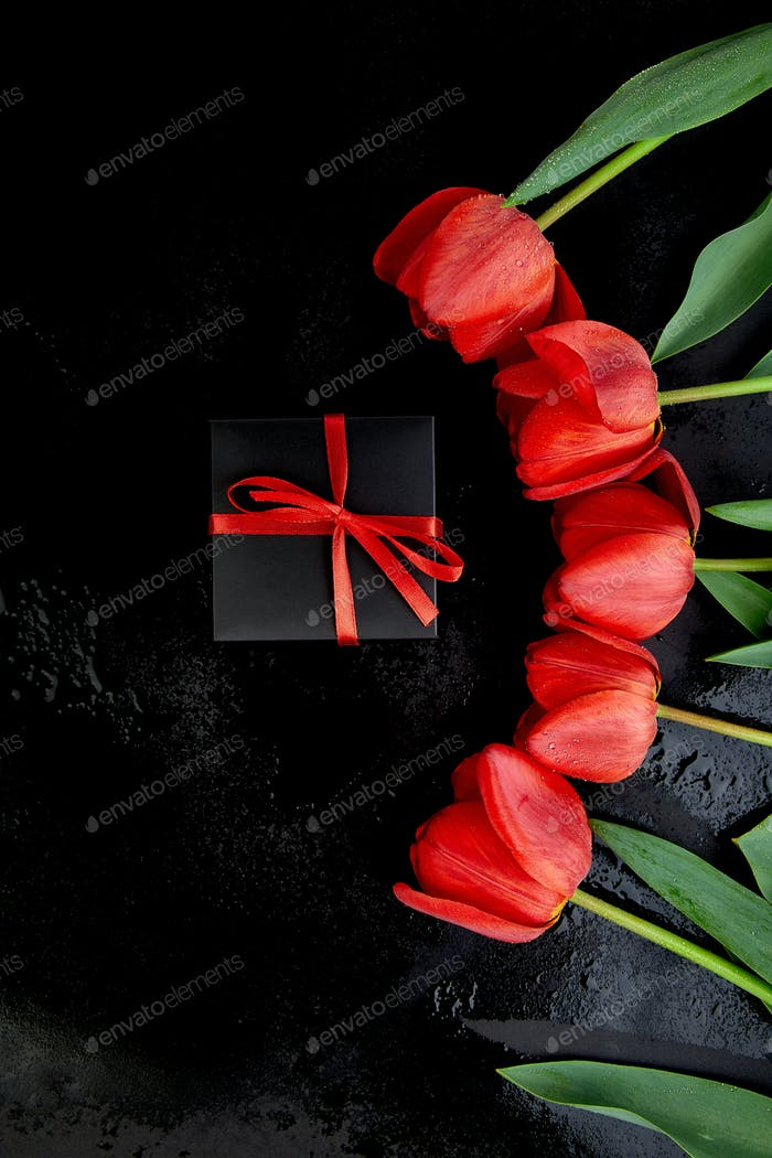 Black gift box with red ribbon near red tulip