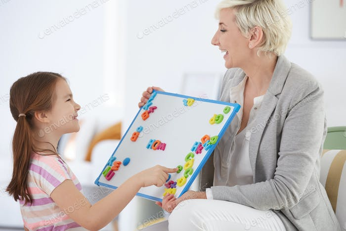 Girl learning alphabet with tutor
