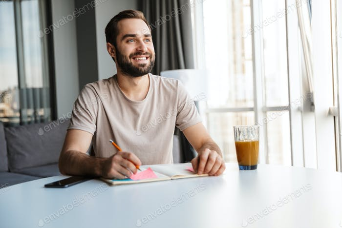 Handsome smart man taking notes