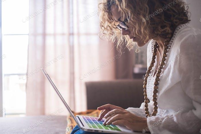 Mujer caucásica adulta concentrada trabajando en un ordenador portátil sentado en el sofá en casa