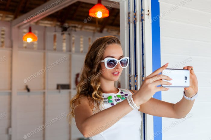 attractive woman in white dress in summer cafe in sunglasses using phone taking photo
