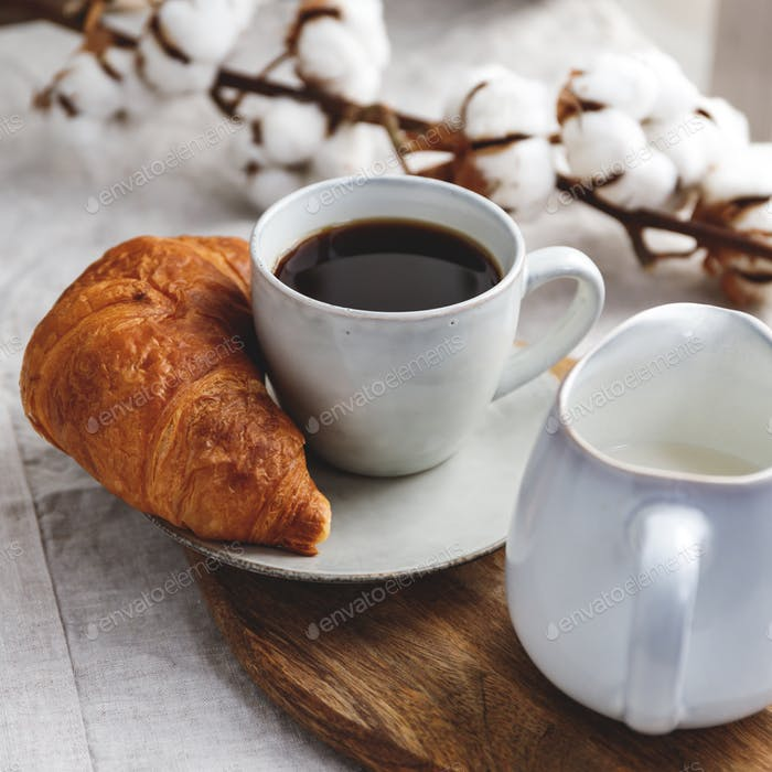 Breakfast table, a cup of black coffee with croissant and milk.