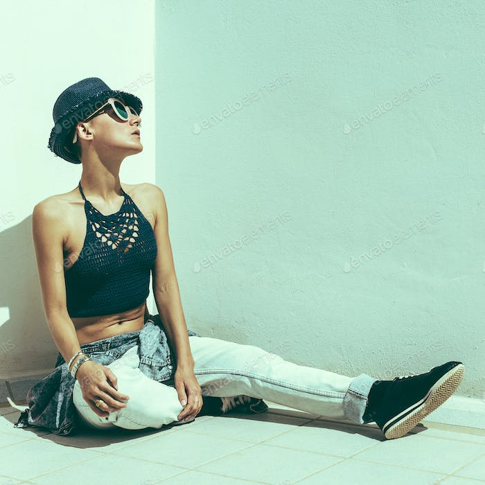 Woman traveler hipster a white wall. Relax Beach outfit fashion