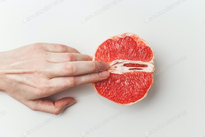 Sexual and female genital concept. Grapefruit and women's fingers like vagina and clitoris