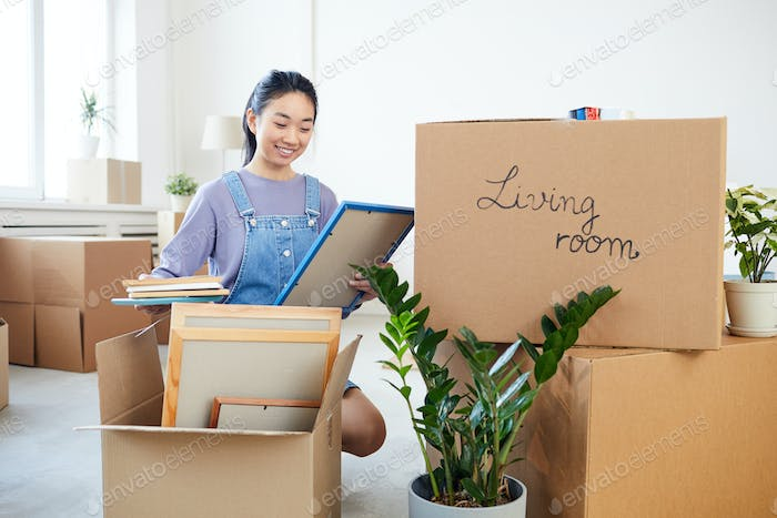 Asian Woman Unpacking Boxes in New Home