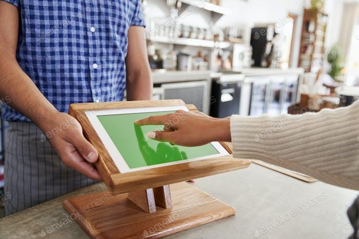 Клиент с помощью сенсорного экрана торгового терминала в кафе, закрыть