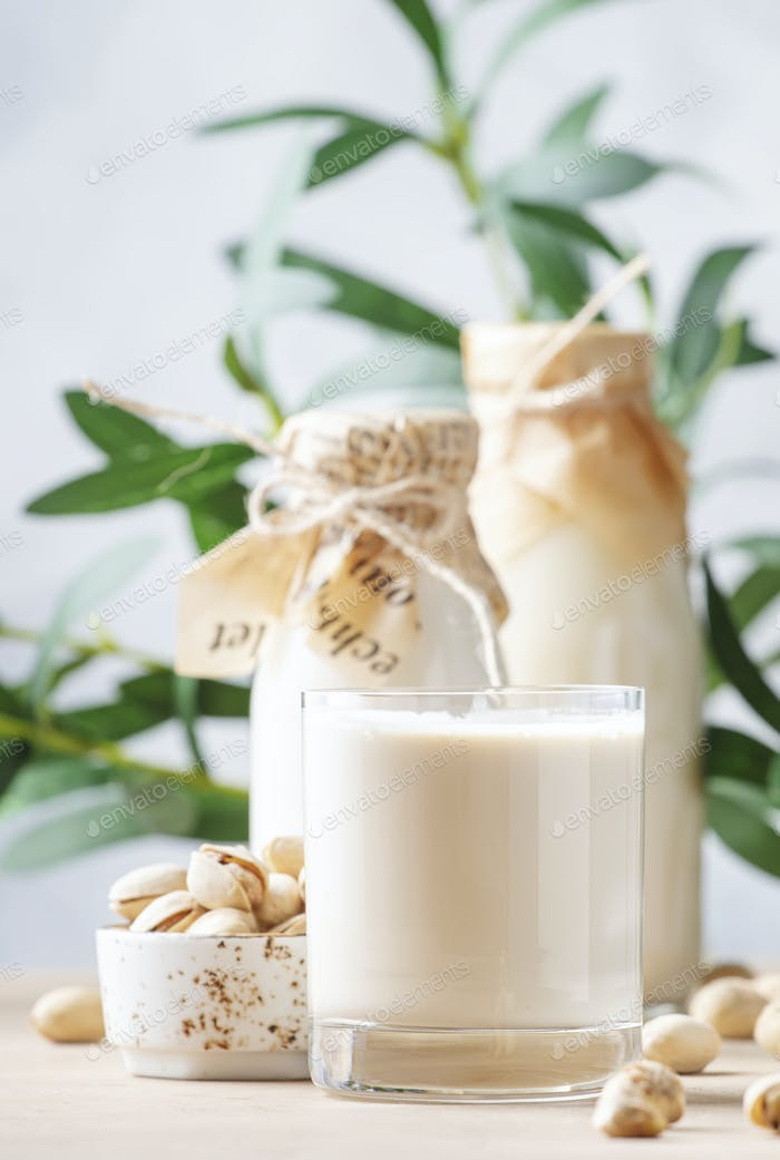 Vegan Pistachio nut milk in bottles, closeup, beige table