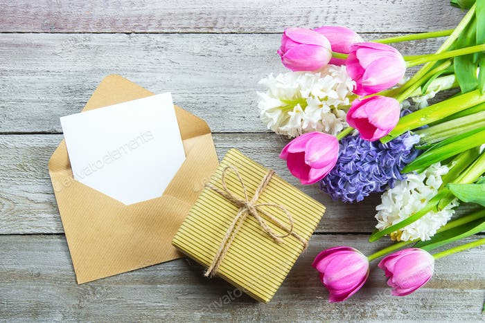 Mockup Mother's day Concept. Spring flowers tulips and hyacinth, gift box and empty card