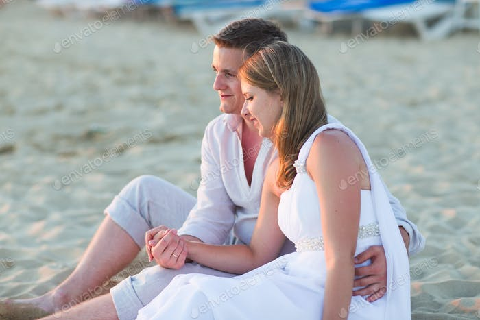 Young love couple sitting together on beach