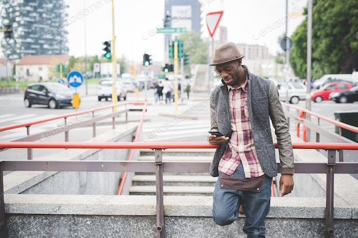 Kniefigur der jungen gutaussehenden afro schwarzen Mann lehnte sich auf ein handra