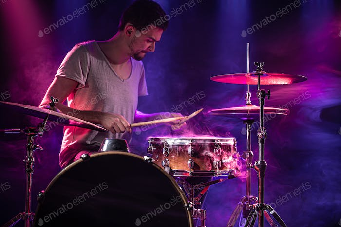The drummer plays the drums. Beautiful blue and red background, with rays of light.