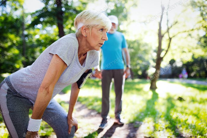 Happy mature couple stretching during running in the park